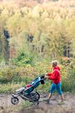 Walking mother with stroller enjoying motherhood at autumn sunse. Walking mother with child in stroller enjoying motherhood at autumn sunset and mountains Stock Photo