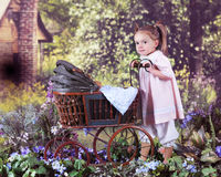 Walking My Teddy. An adorable preschooler pushing her teddy in an antique doll carriage toward a rustic old homestead on a bright summer day Royalty Free Stock Photo