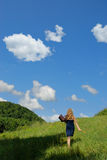 Walking with Nature. Female walking up a hill in a green meadow against blue, cloudy sky Stock Photography