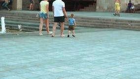 Walking near the fountain in the city park. Walk through the city park. People walk in the park. The boy skates on a skateboard. Fantan in the city park stock footage