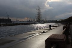 Walking near the Neva. Embankment of Schmidt in St. Petersburg. Walking in the background of a sailing ship, near a museum in a submarine, the waters of the Royalty Free Stock Image