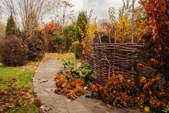 Walking in november garden. Late autumn view with rustic fence Stock Photo