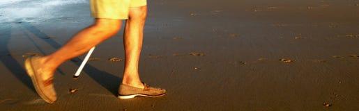 Walking old man. Oldman walking along the beach Royalty Free Stock Images