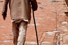 Walking old man with the stick. On the brick pavement Royalty Free Stock Image