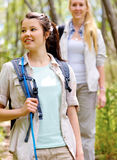 Walking outdoors with backpacks. Two beautiful attractive women hiking outdoors in the woods. healthy active lifestyle concept stock image