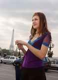Walking in Paris. Young woman standing on Paris street, blurred Eiffel tower in background royalty free stock photo