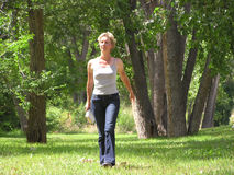 Walking in Park. Young woman walking in park in jeans and top Royalty Free Stock Photos