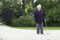 Walking in the park. Elderly woman taking a walk with the aid of a walking stick stock photo