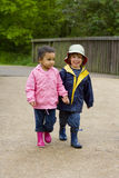 Walking Through The Park. A little boy and girl wearing wellington boots holding hands and walking through a country park Royalty Free Stock Photos