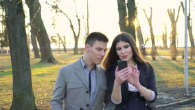 Walking in the park by colleagues with smartphone stock video