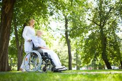 Walking in park. Pretty nurse walking with senior patient in a wheelchair in park Royalty Free Stock Image