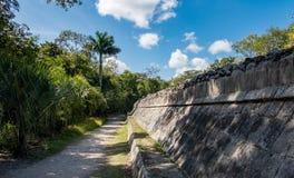 Walking path along ancient stone wall among Mayan ruins of Chichen Itza in Mexico royalty free stock photo
