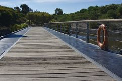 Wooden walking path in bridge across lake. In Cranbourne Australia during daytime on sunny day royalty free stock photo