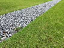 Walking path in a grass field. Gray gravel walking path in a grass field/lawn of a garden Royalty Free Stock Photo