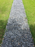 Walking path in a grass field. Gray gravel walking path in a grass field/lawn of a garden with shadow of a tree Stock Photo