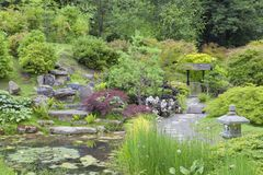 Walking path through oriental garden with pond, rocks, lantern