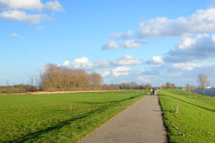 Walking path over an embankment along a wide Dutch river Stock Image