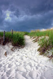 Walking Path over Sand Dune under Stormy Sky Stock Photo