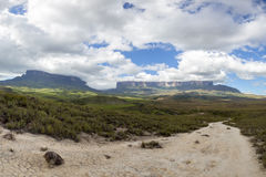 Walking path to Kukenan tepui or Mt Roraima in Venezuela. Walking path going to Mt Roraima or Kukenan tepui early with clouds and blue sky, Gran Sabana in Royalty Free Stock Photography