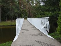 Walking path and white metallic bridge in park, Lithuania royalty free stock images