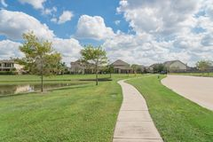 Residential houses by the lake in Pearland, Texas, USA. Walking pathway alongside leads to residential houses by the lake in Pearland, Texas, USA Royalty Free Stock Photography