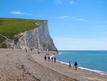 Walking on pebble beach near white cliffs of Seven Sisters, East Sussex, England Royalty Free Stock Photo