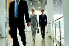Walking people. Businesspeople going along corridor inside office building stock photos