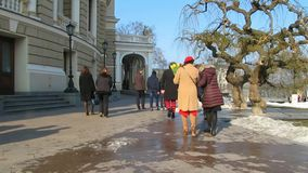 Walking people in the city. People of different age pass near Opera theater. Spring. March 8. Holiday Day stock footage