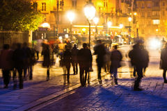 Walking people at night in Paris. Near Notre Dame a crowd of people, shown in motion blur and silhouette, walking on a cobblestone square near Notre Dame Royalty Free Stock Image