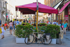 Walking people and outdoor cafe with bicycle near it in Rimini Stock Photos