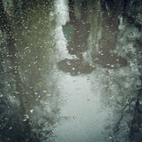 Walking people, reflection in the wet asphalt - vintage effect. Royalty Free Stock Photo