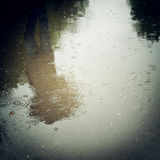 Walking people, reflection in the wet asphalt - vintage effect. Rainy day photo with retro filter Stock Images