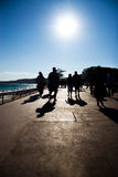 Walking people silhouettes on sea coast Stock Images
