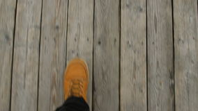 Walking on a pier at the beach, POV shot of a man with yellow shoes. Walking on a pier at the beach, POV shot of a man with yellow autumnal boots stock video footage