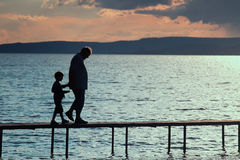Walking on the pier. The men and the boy are walking carefully on the pier Royalty Free Stock Photo