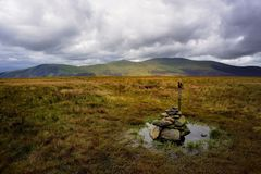 Walking Poles and cairn on Mungrisdale Common. Dark clouds over Skiddaw Ridge Stock Photo