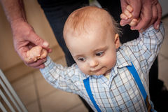 Almost walking. Portrait of a adorable baby boy holding his mother's hand while learning to walk Royalty Free Stock Images