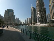Walking Promenade at Dubai Marina with view of skyline, buildings and yacht stock image