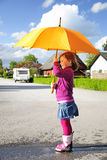 Walking after rain. Pretty young girl have fun with umbrella and wellingtons Stock Images