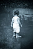 Walking in the rain. Little child in a puddle - monochrome, blue toning, vignette Stock Photo