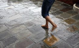 Walking in the rain. Young tourist girl walking in the rain along one of the canals of Venice, Italy. Motion blur Stock Photo