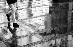 Walking on a rainy day. A person walking in the city pedestrian zone on a rainy day, from waist down, in black and white, with reflections Royalty Free Stock Image