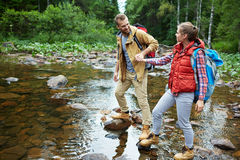 Walking through river. Couple of adventurers passing through river on stone-path Stock Photo