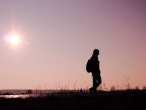 Walking on the road. Silhouette of a woman with a backpack walking on the road Stock Images