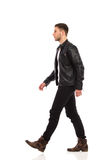 Walking rock man. Walking man in black leather jacket and black jeans. Full length studio shot isolated on white stock photos