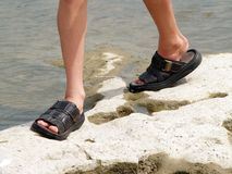 Walking on Rocks. Picture of Youth walking on rocks by a river stock photography