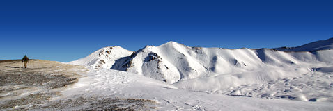 Walking on the roof of the World panoramic. Beautiful Snow covered mountains and a lonely man Stock Photography