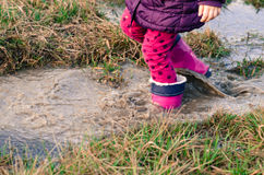 Walking in rubber boots in autumn puddle Royalty Free Stock Images