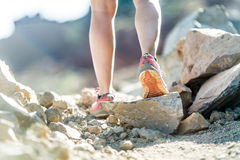Walking or running legs, adventure and exercising. Walking or running legs on trail, adventure and exercising in mountains nature, runners sports shoe on dirt royalty free stock image