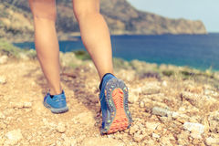 Walking or running legs in forest, adventure and exercising. Walking running hiking or exercising, sports shoe and legs on rocky hiking trail in mountains stock photography
